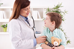 Beautiful female doctor examining smiling child Royalty Free Stock Image