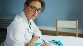 Beautiful female doctor in glasses fills the patient`s medical history, and then looking at the camera and smiling. Healthcare and medicine concept stock footage
