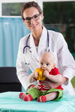 Beautiful female doctor with little baby patient Stock Images