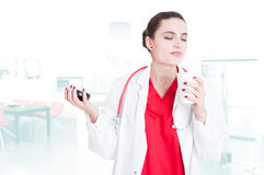 Beautiful female doctor relaxing with coffee Royalty Free Stock Photos