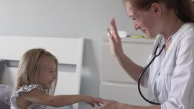 Beautiful female doctor says goodbye to a child after examination. stock footage