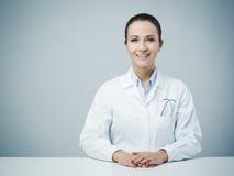Beautiful female doctor sitting at desk Stock Photo