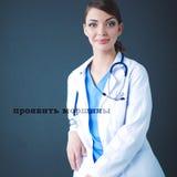 Beautiful female doctor sitting on stool isolated grey background Stock Photos
