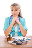 Beautiful female doctor sitting at table and looking at camera Stock Photo