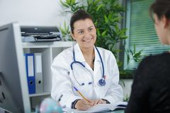Beautiful female doctor smiling to patient at office Royalty Free Stock Image