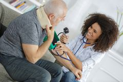 Beautiful female doctor testing patients blood pressure Royalty Free Stock Images
