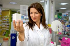 Beautiful female doctor in uniform holding medicine in pharmacy smiling Royalty Free Stock Photography