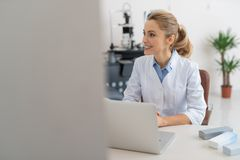 Beautiful female doctor using white notebook at work stock photo