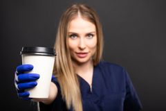 Beautiful female doctor wearing scrubs drinking takeaway coffee. On black background with copypsace advertising area Royalty Free Stock Images