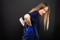 Beautiful female doctor wearing scrubs making back pain gesture. On black background with copypsace advertising area Stock Images