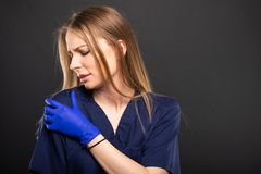 Beautiful female doctor wearing scrubs making shoulder pain gest. Ure on black background with copypsace advertising area Stock Photo