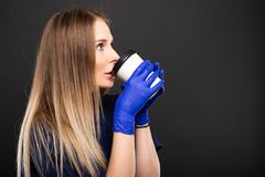 Beautiful female doctor wearing scrubs showing coffee cup. On black background with copypsace advertising area Stock Images