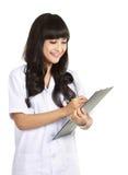 Beautiful female doctor writing Royalty Free Stock Photo