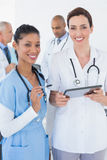 Beautiful female doctors working together with tablet Stock Photography