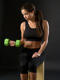 Beautiful female doing dumbbell curl. Photo of an attractive female doing a dumbbell curl while sitting Stock Image