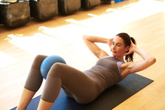 Beautiful female is doing pilates. Fit woman is doing sit ups with medicine ball between her legs Stock Photos