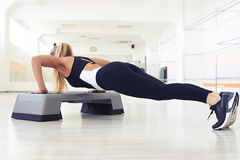 Beautiful female doing push-ups on the step platform Stock Photos