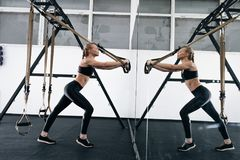 Sporty woman doing TRX exercises in the gym Royalty Free Stock Photography