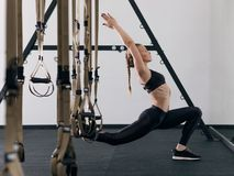 Sporty woman doing TRX exercises in the gym Stock Photos