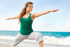 Beautiful female doing yoga warrior pose Royalty Free Stock Photography
