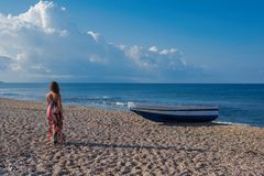 Beautiful female in the dress  near boat on the sand. Beautiful female in dress near boat on the sand on sunset Royalty Free Stock Photography