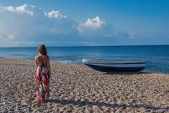 Beautiful female in the dress  near boat on the sand. Beautiful female in dress near boat on the sand on sunset Stock Photos
