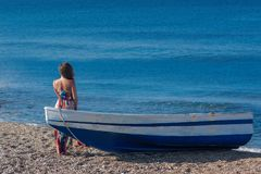 Beautiful female in the dress  near boat on the sand. Beautiful female in dress near boat on the sand on sunset Stock Photography