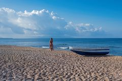 Beautiful female in the dress  near boat on the sand. Beautiful female in dress near boat on the sand on sunset Royalty Free Stock Photo