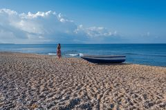 Beautiful female in the dress  near boat on the sand. Beautiful female in dress near boat on the sand on sunset Royalty Free Stock Photos
