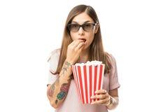 Beautiful Female Eating Popcorn While Watching 3D Film. Portrait of beautiful female eating popcorn while watching 3D film over white background stock image