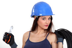 Beautiful female electrician. Holding cutters and extension cord Stock Images