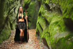 Beautiful female elf archer in the forest hunting with a bow. Full length shot of a beautiful blonde haired young woman elf wearing a green cape standing in the Stock Images