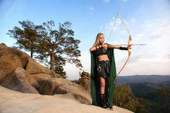 Beautiful female elf archer in the forest hunting with a bow. Full length shot of a female elf archer preparing to shoot standing on top of a rock beautiful Royalty Free Stock Images