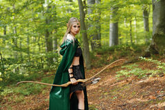 Beautiful female elf archer in the forest hunting with a bow. Beautiful young female elf looking to the camera over her shoulder while wandering at the woods Royalty Free Stock Images