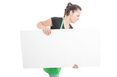 Beautiful female employee carrying big blank poster Royalty Free Stock Photo