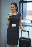 Beautiful female executive standing with luggage while having juice in corridor. Of office Stock Photos