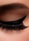 Beautiful female eye with extreme long eyelashes, black liner makeup. Perfect make-up, long lashes. Closeup fashion eyes Stock Photos