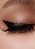 Beautiful female eye with extreme long eyelashes, black liner makeup. Perfect make-up, long lashes. Closeup fashion eyes. Beautiful macro shot of female eye with Royalty Free Stock Photo