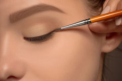 Beautiful female eyes with make-up and brush royalty free stock photography