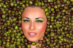 Beautiful female face in gooseberry Stock Photo