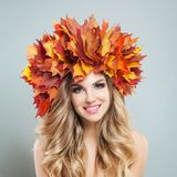 Beautiful female face. Happy woman with autumn leaves crown, makeup and blonde curly hairstyle royalty free stock images