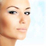 Beautiful female face over blue sky background Stock Photos