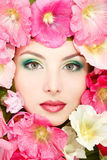 Beautiful female face with pink, red and white mallow flowers fr. Beauty portrait of beautiful female face with pink, red and white mallow flowers frame Royalty Free Stock Image