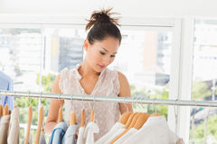 Beautiful female fashion designer with rack of clothes Royalty Free Stock Photo