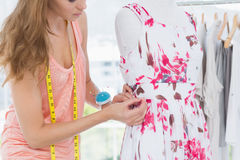 Beautiful female fashion designer working on floral dress Royalty Free Stock Photography