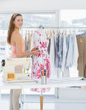 Beautiful female fashion designer working on floral dress at studio Royalty Free Stock Photos