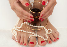A beautiful female feet and arms with red pedicure and manicure  on white and decorated with pearls Royalty Free Stock Photography
