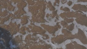 Beautiful female feet on the beach against the background of the sea, waves, foam, sand and pebbles. View from above. The concept of travel, tourism. Slow stock footage