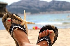 Beautiful female feet on the beach. In the vivid summer shoes Royalty Free Stock Photos