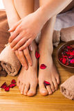 Beautiful female feet and hands, spa salon, pedicure and manicure procedure. With petals of red rose flower royalty free stock images
